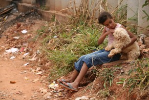 Boy and dog outside mobile vet clinic in Brazil
