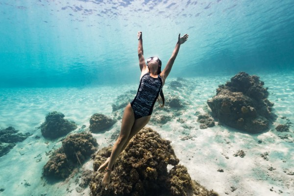 Woman swimming in OceanPositive suits made from ECONYL®, a fabric made from recycled plastic fishing gear.