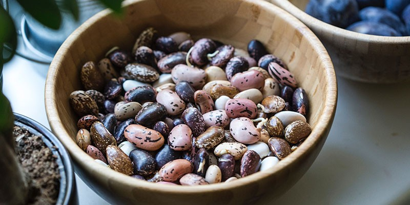 A wooden bowl full of dried beans of different varities