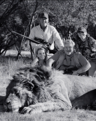 Group having their photo taken with a dead lion.