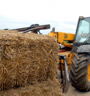 A tractor carries a bale of hay