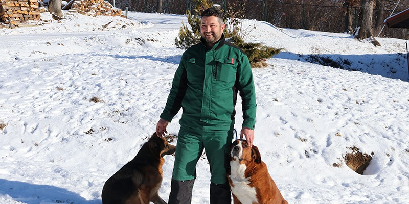 Florin wears a pair of green overalls and stands in a field covered in snow. To his left, Betty, his rescue St Bernard mix and to his right there's another large dog who lives at the sanctuary.