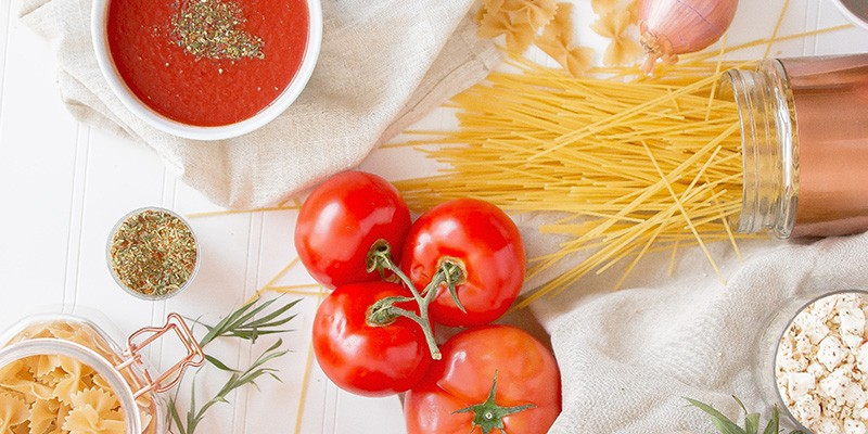 A white tablecloth with a spread of ingredients to make tomato pasta: tomato sauce, fresh tomatoes and raw spaghetti