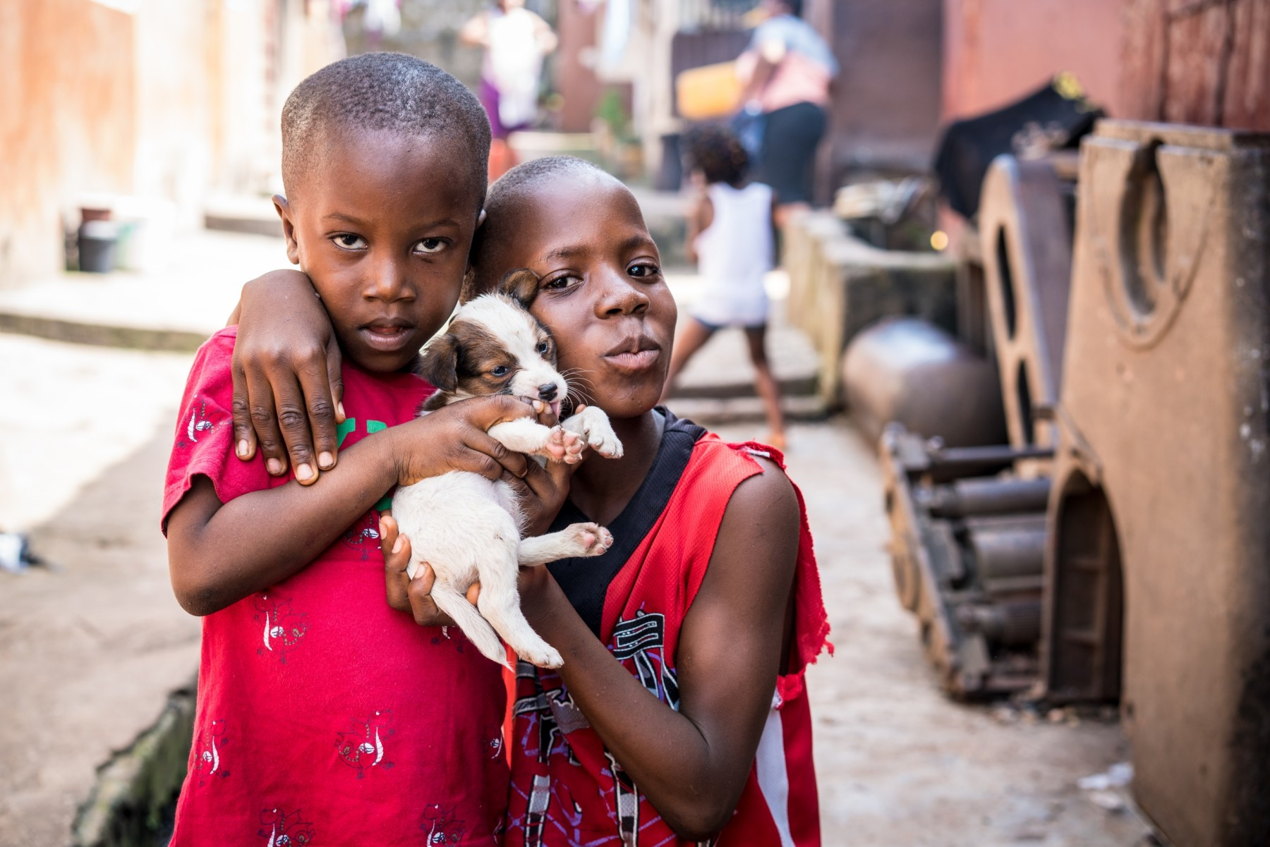 Two children holding small puppy - World Animal Protection