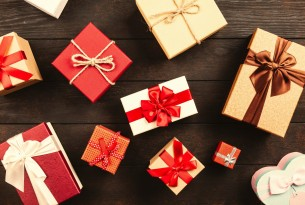 Several gold and red wrapped gifts sitting on a dark brown table.
