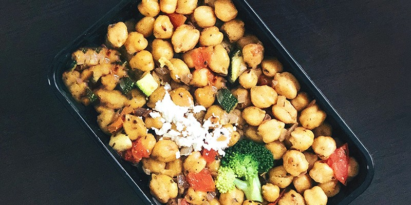 A rectangular baking tray filled to the heap with chickpeas. Mixed with the beans you can see herbs, and chunks of red pepper and broccoli.