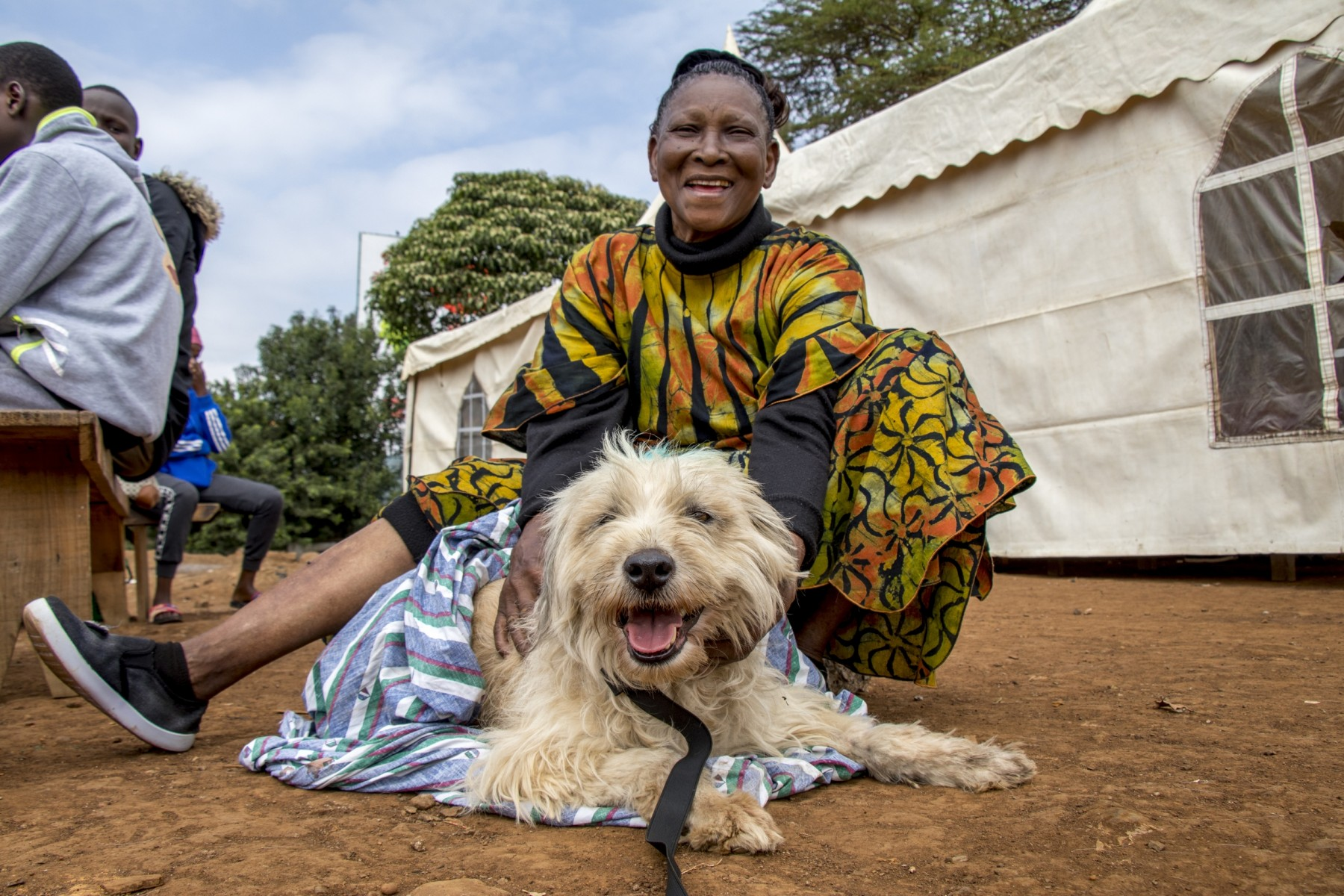 Dog sitting with its owner at rabies vaccination drive in Kenya - World Animal Protection