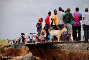 Locals stand beside a damaged section of the road with a goat after Cyclone Idai