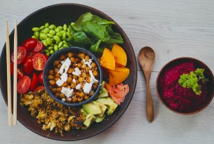 A spread of plant-based food: a large bowl containing a smaller bowl full of chickpeas, surrounded by avocados, tomatoes, edamame beans, spinach and sweet potato. Next to it, a smaller bowl filled with bright purple beetroot dip.