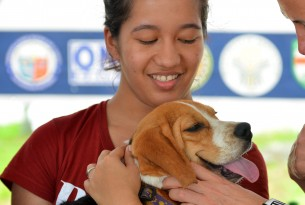 Jenny May holding a dog during visit to the Philippines