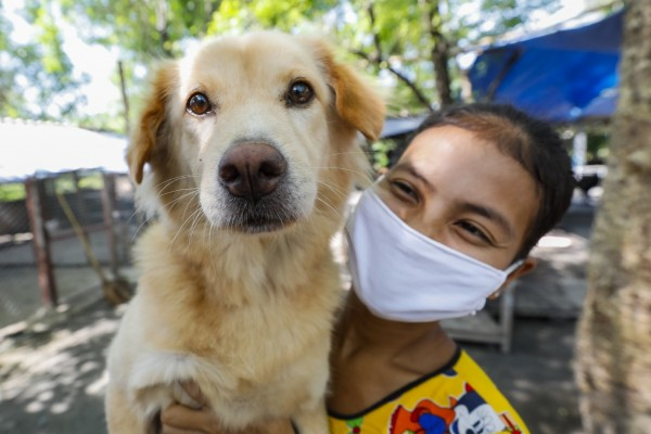 Caretaker at Wat Hua Kho temple in Thailand holding a dog - World Animal Protection