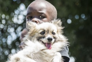 A young boy posing with his dog in Mombasa, Kenya - World Animal Protection - Better Lives For Dogs