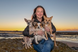 A woman sits on a beach holding three rescue dogs