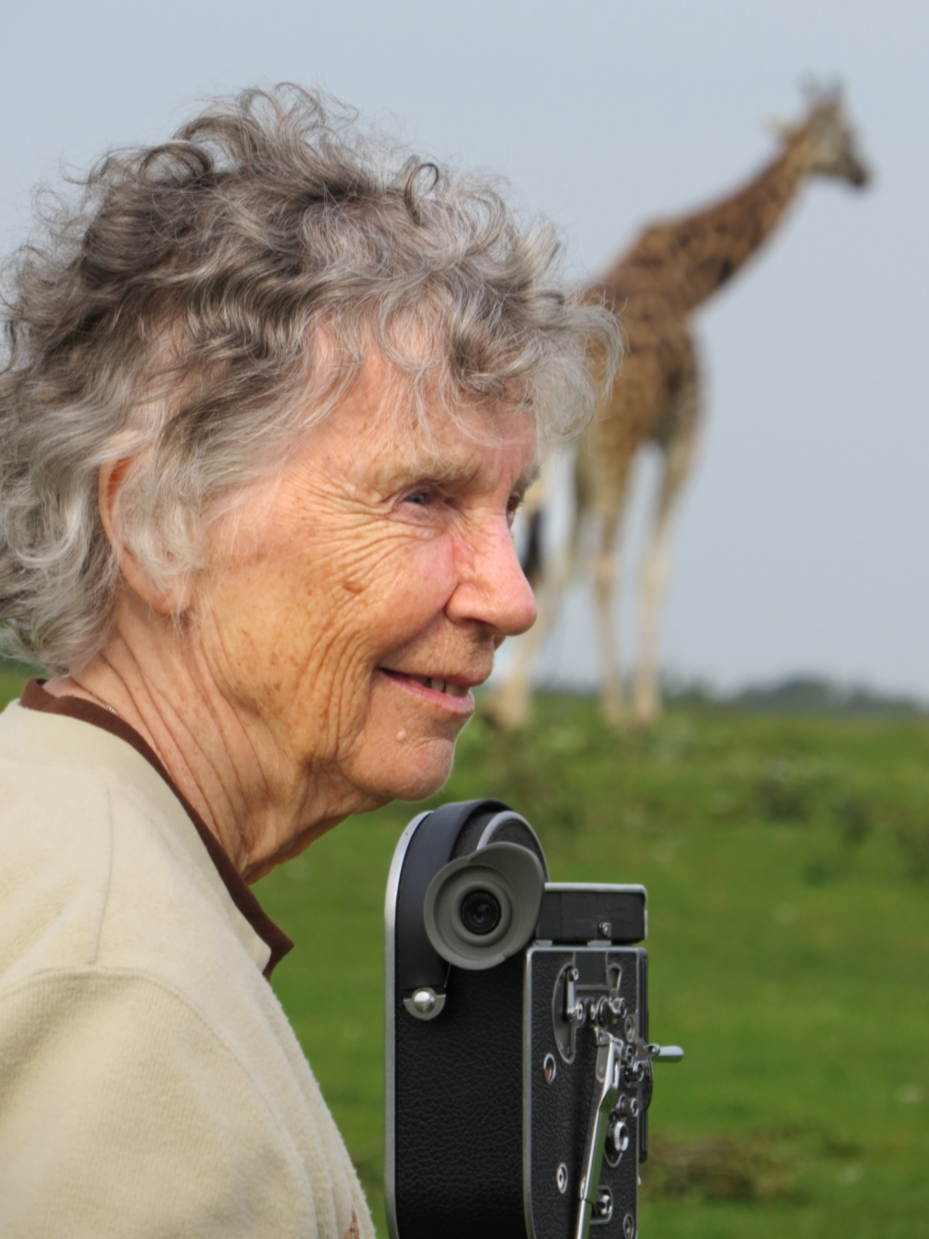 A portrait of Dr. Anne Innis Dagg with a giraffe in the background