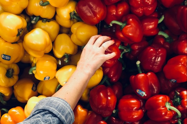 A hand picking vegetable from a wall of colourful red and yellow peppers