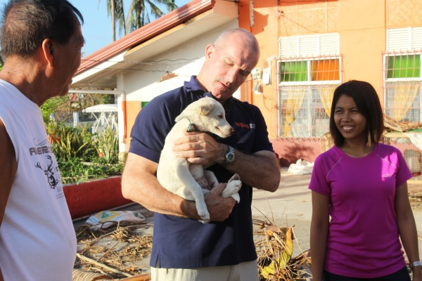 Dr. Ian Dacre checks on a puppy belonging to the Bante family in the northern part of Cebu Island, Philippines