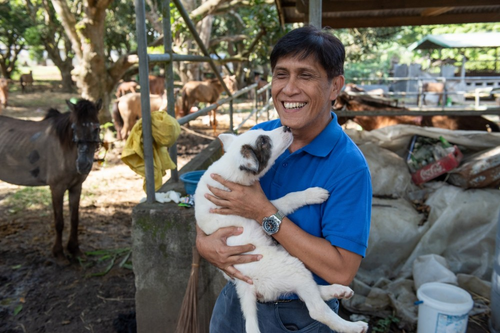 A man with a dog at an animal rescue shelter in the city of Lipa, Batangas