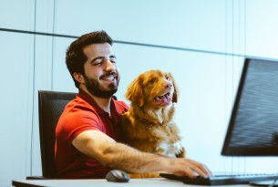 A man sits in front of a computer with a dog on his lap. He reaches for the keyboard as the dog loks at the screen.