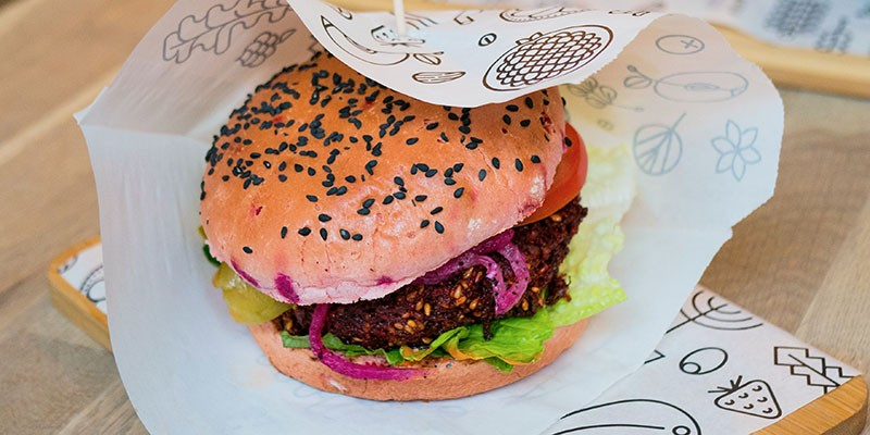 A vegetarian burger in a bun with colourful garnishes, served on white greaseproof paper with black and white designs of vegetables