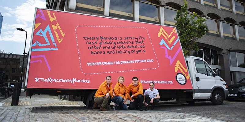 World Animal Protection staff crouching in front of a large van, displaying a campaign calling out Nando's on their animal welfare